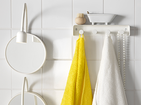 A white battery-operated LED wall lamp with mirror, shown together with a white towel rack and towels in yellow and white.