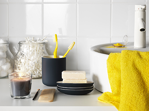 A black toothbrush holder with two yellow toothbrushes and a soap dish with soap bars, shown on a bathroom counter.