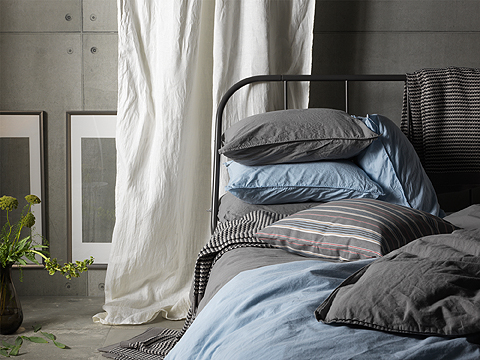 Close-up of a black metal bed with bedlinen in light blue and grey.