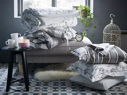 A pile of bedlinen in different patterns on a footstool and a black round side table with white mugs and a lit scented candle.