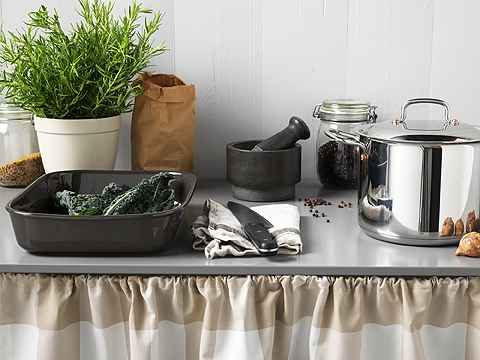 A black oven dish with vegetables shown together with a black mortar, a kitchen knife and a stainless steel pot with lid.