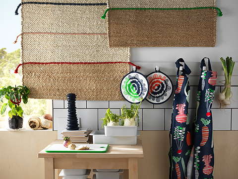 Two aprons and two pot holders with colorful pattern, hung on a kitchen wall.