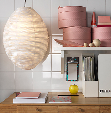 A desk with white magazine files and round light pink boxes with three levels of storage in each box, shown together with an oval rice paper lamp.