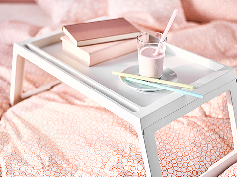 A white bed tray with two books and a glass with strawberry smoothie and three straws in pink, yellow and light blue.