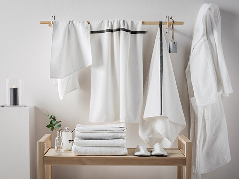 A wooden rod on a wall with white towels and a bench with a pile of towels and a pair of slippers.