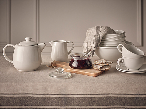 A set table with teapot, milk jug, teacups and bowls, all in white stoneware.