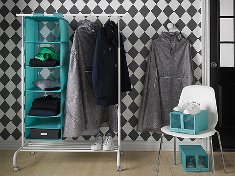 A clothes rack on castors shown together with a light blue clothes storage with six compartments and shoe boxes with mesh window.