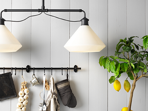 A black pendant lamp with double shades in white painted glass, a black rail with kitchen utensils, and a lemontree.