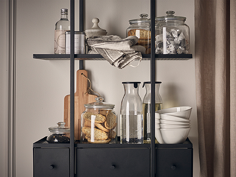 A black wall shelf with glass jars filled with biscuits, clear glass carafes with water and white bowls.