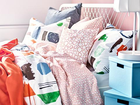 A bed filled with colourful bedlinen in orange, green, blue and white.