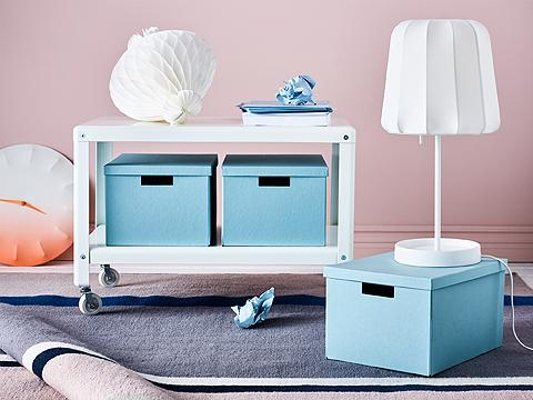 A white side table on castors with light blue storage boxes shown together with a white table lamp.