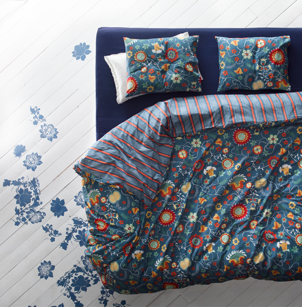A bed with a quilt cover and two pillowcases in blue with floral pattern on one side and stripes on the other.