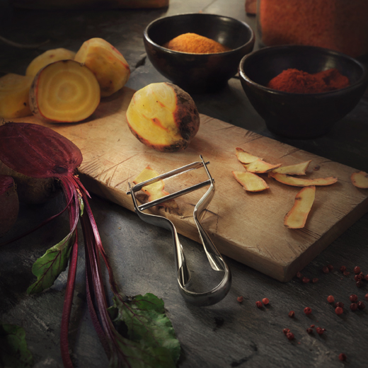 A stainless steel peeler shown together with a wooden chopping board and peeled root vegetables.