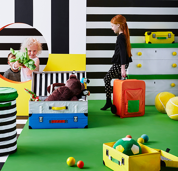 Children playing and packing toys in trunks for toys that looks like real suitcases.