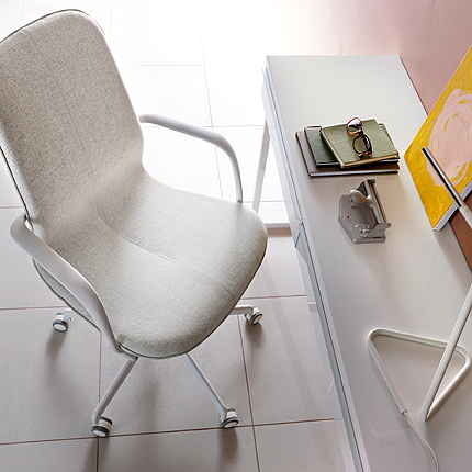 A swivel chair with beige seat combined with white armrests and legs on castors. Shown together with a white desk.
