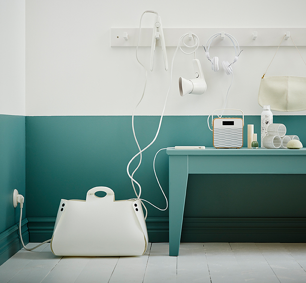 A white cable management bag in the shape of a handbag, shown with cords hanging out.