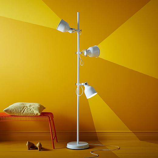 A white floor lamp with three spots directed in different ways.