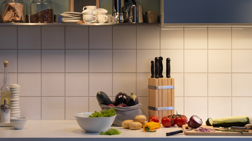 Well-lit countertop filled with different coloured vegetables and kitchen accessories.