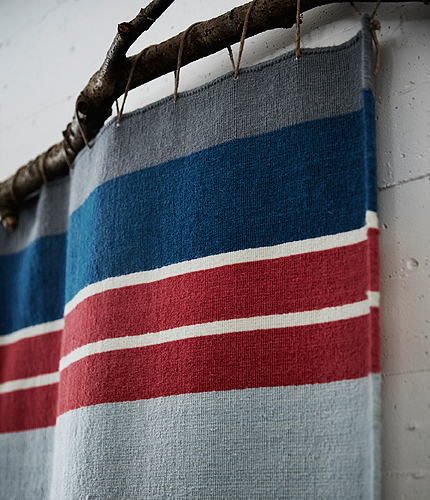 Close-up of a colourful striped wool rug, hung on the wall as a decoration.