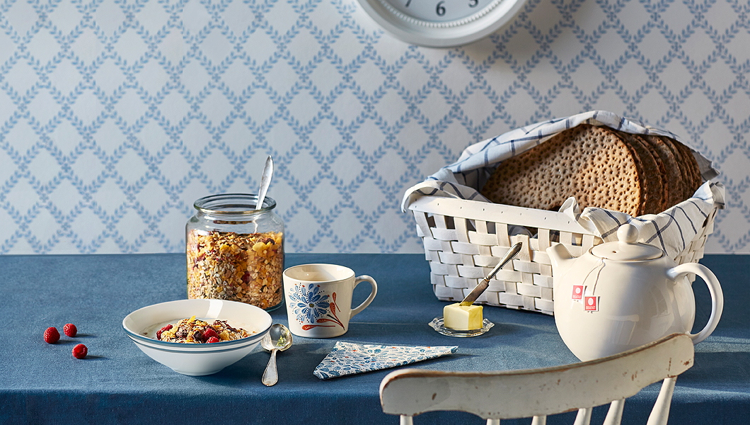 A breakfast table laid with a blue stoneware bowl with cereals and yoghourt, an off-white mug filled with tea and a white woven basket with crispbread in a tea towel.