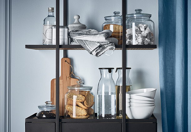 A black kitchen shelf with glass jars filled with tea bags and rusks, glass carafes with water and bowls in off-white stoneware.