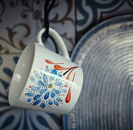 Close-up of an off-white mug in stoneware with blue floral pattern.