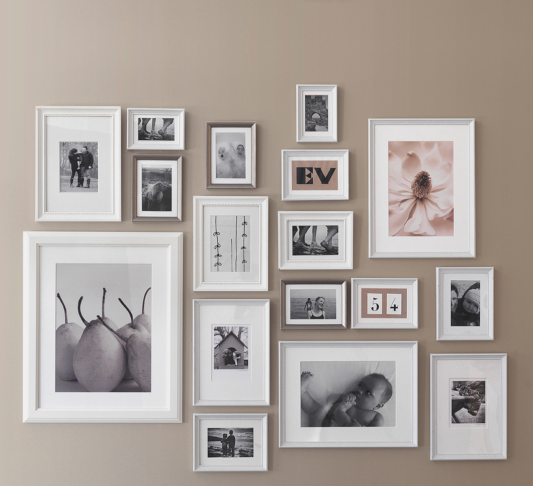 A wall, decorated with white and silver-coloured picture frames in different sizes. Shown together with family photos and posters.