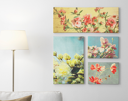 A living room wall, decorated with four pictures, two large and two small, with yellow, red and pink flower motifs.