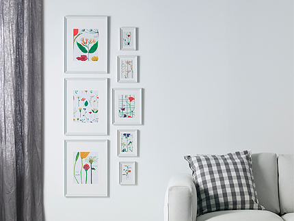 A living room wall, decorated with eight white picture frames with floral pattern pictures, three large and five small.