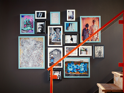 A brown wall, decorated with blue, white and black picture frames in different sizes. Shown together with posters and family photos.