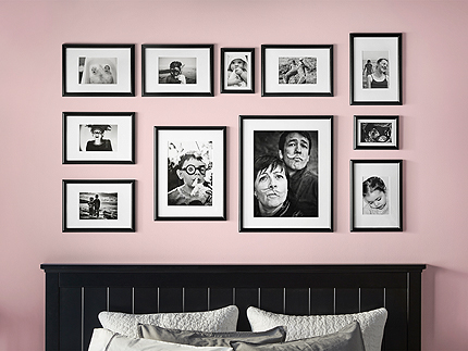 A pink bedroom wall, decorated with black picture frames in different sizes. Shown together with family photos.