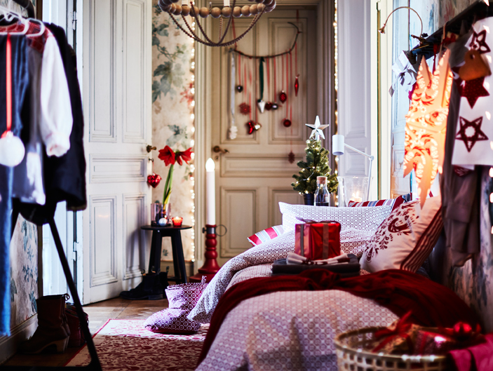 A decorated bedroom with bedlinen in white/red, a large Christmas star, a floor candelabra and wrapped Christmas presents.