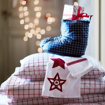 A pile of bedlinen in red/white, white guest towels with red stars and blue slippers with presents.