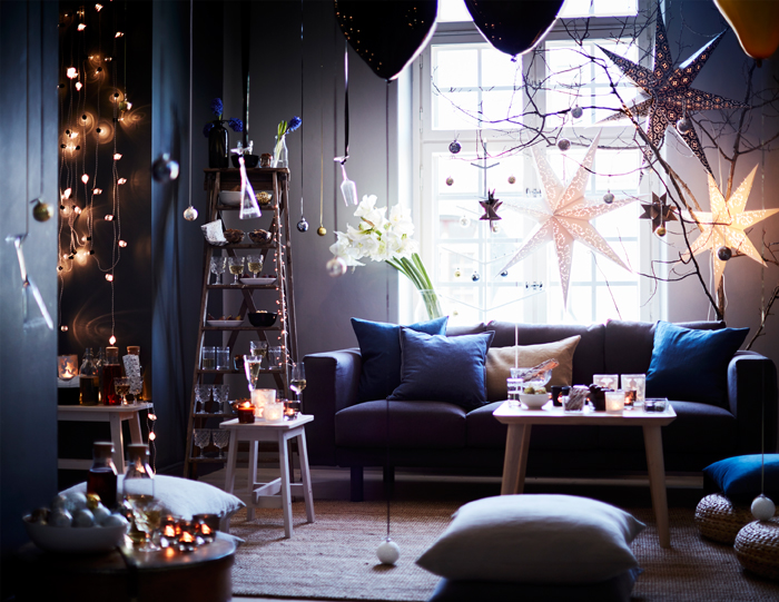 A decorated livingroom with lit candles on the coffee table, a lighting chain on the wall and three large Christmas star by the window.