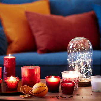 A coffee table with lit candles and a glass dome with a small lit lighting chain.
