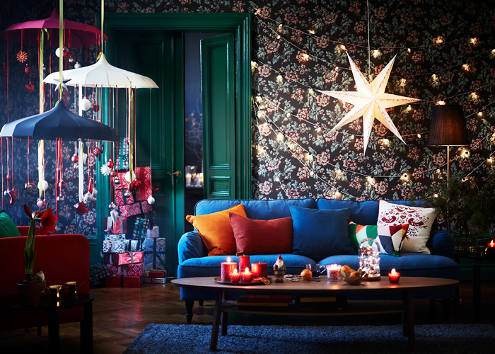 A decorated livingroom with lit candles on the coffee table, a lighting chain on the wall together with a large Christmas star.