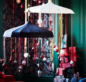 Two umbrellas hanging from the ceiling, decorated with red ribbons and baubles in white, red and silver-colour.