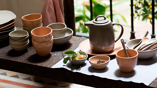 A display of stoneware jars, plates, bowls, teacups, teapot and spoons in light pink and grey.