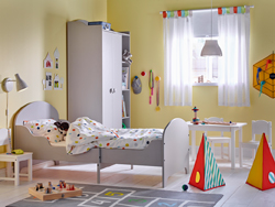 Childrens bedroom with yellow walls and light gray extended bed and wardrobe.