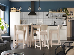 Two bar tables and five barstools in birch in a blue, white and light wood kitchen.