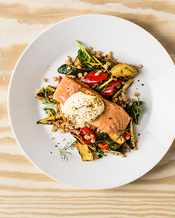 ASC-certified Salmon fillet served with grilled vegetables and wheat pilaf.