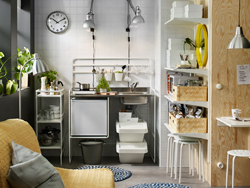 A small white mini-kitchen with a small fridge. Combined with a cart and wall shelves for extra storage.