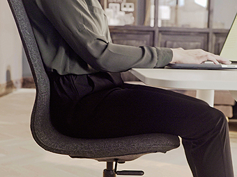 Side view of a woman at a workstation sitting on an ergonomic LÅNGFJÄLL chair. The hidden tilt tension mechanism under the chair lets you adjust the height and the posture in order to find a comfortable position.