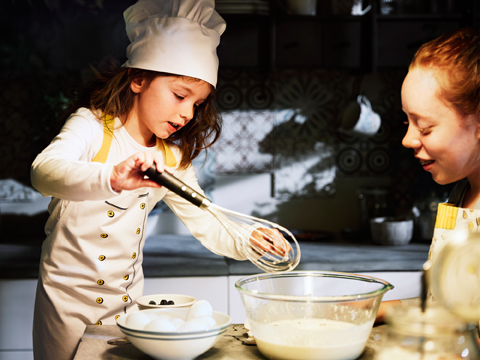 Two girls baking cookies, one of the girls is wearing a chef's hat and an apron.