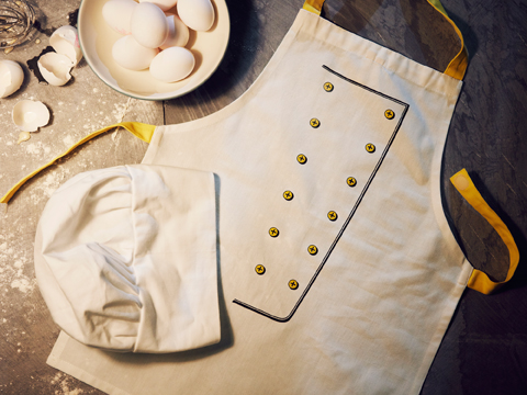 A chef's hat and an apron with touch-and-close fastening which easily loosens if the child gets stuck