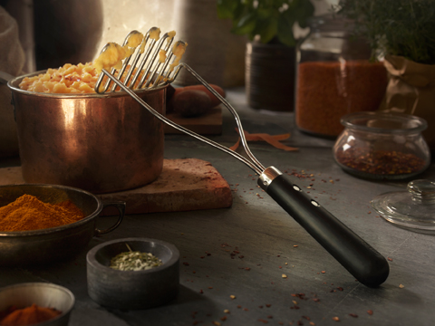 A potato masher in stainless steel with a black plastic handle. Shown together with a pot filled with mashed potatoes.