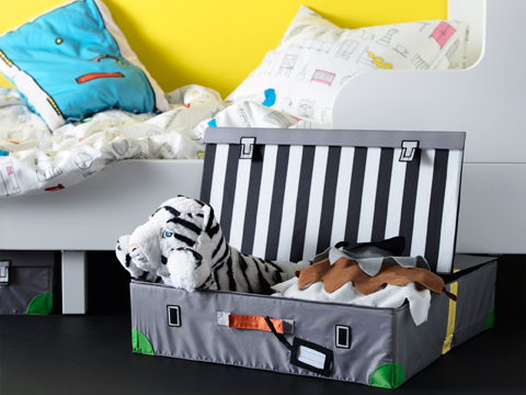 A trunk for toys that looks like a real suitcase filled with soft toys.