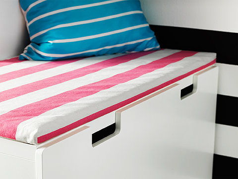 A white bench with a striped bench pad in pink and white.