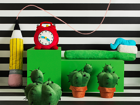 A display of soft toys in the shape of a oversized pen, toothbrush with toothpaste, cactus in a plant pot and a clock with moveable hands.