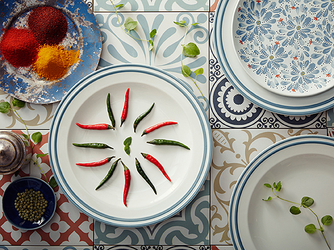 An off-white stoneware plate with blue lines around the edge. Decorated with red and green chili peppers.